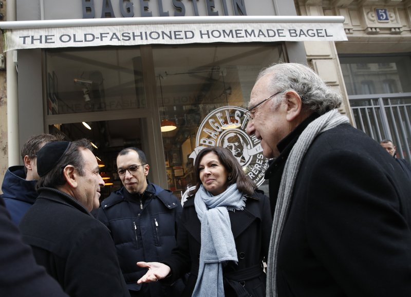 Paris mayor Anne Hidalgo, second right, talks with the President of the Central Jewish Consistory of Paris Joel Mergui, left, as district mayor Pierre Aidenbaum, right, looks on outside the bagel shop which was sprayed with the German word