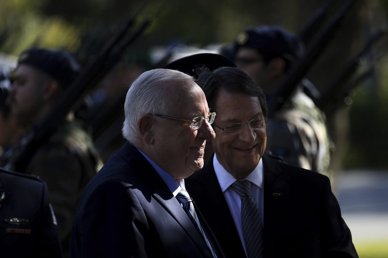 Cyprus' president Nicos Anastasiades and Israel's President Reuven Rivlin, left, review a military guard of honor during a welcoming ceremony at the presidential palace in divided capital Nicosia, Cyprus, on Tuesday, Feb. (AP Photo/Petros Karadjias)