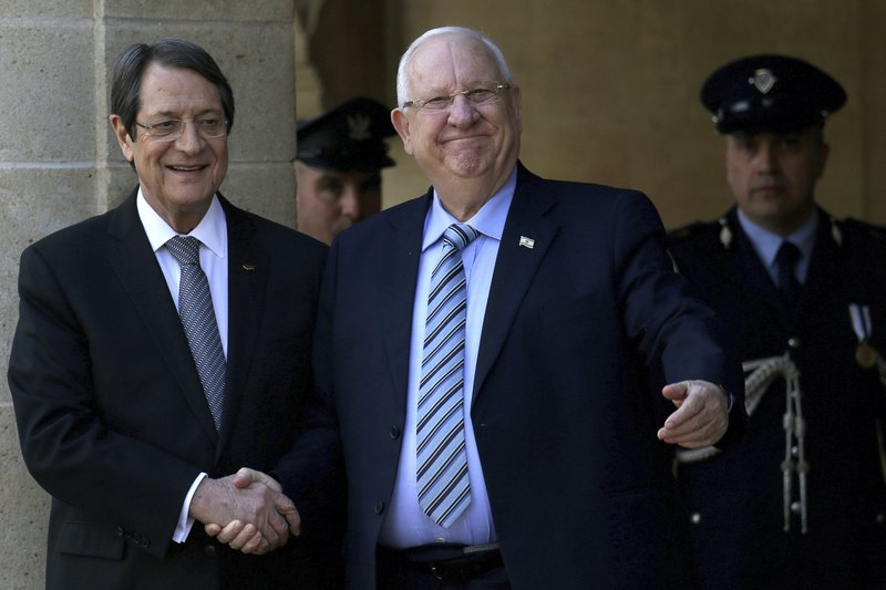 Cyprus' president Nicos Anastasiades, left, and Israel's President Reuven Rivlin, shake hands during a welcoming ceremony at the presidential palace in divided capital Nicosia, Cyprus, on Tuesday, Feb. (AP Photo/Petros Karadjias)