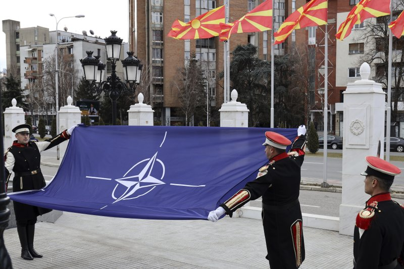 Macedonian soldiers raise the NATO flag in front of the government building during a ceremony in Skopje, Tuesday, Feb. (AP Photo/Dragan Perkovksi)