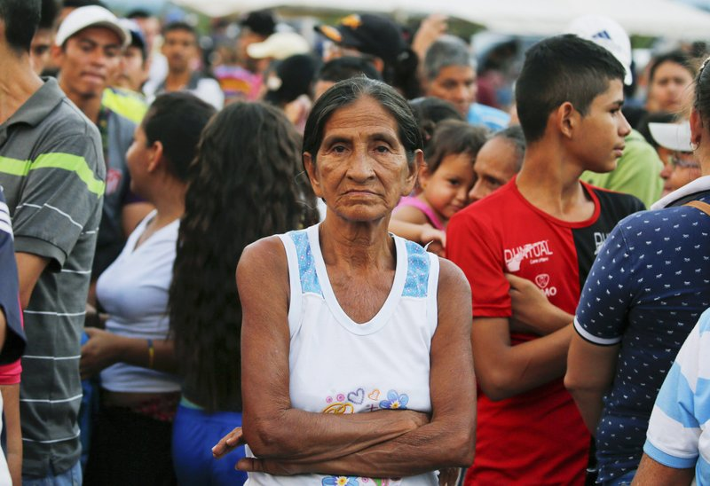 A woman poses for a photo as she lined up to receive bags with food subsidized by the Nicolas Maduro's government near the international bridge of Tienditas on the outskirts of Urena, Venezuela, Monday, Feb. (AP Photo/Fernando Llano)