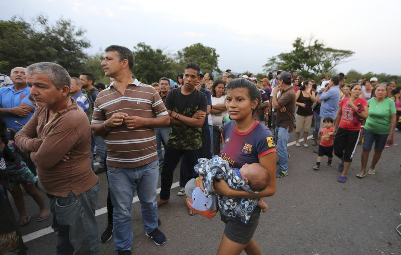 People line up to receive a bag with food subsidized by the Nicolas Maduro's government near the international bridge of Tienditas on the outskirts of Urena, Venezuela, Monday, Feb. (AP Photo/Fernando Llano)