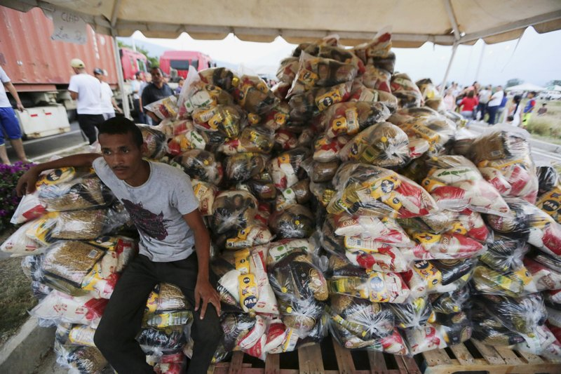 A volunteer takes a break during the distribution of bags with food subsidized by the Nicolas Maduro's government near the international bridge of Tienditas on the outskirts of Urena, Venezuela, Monday, Feb. (AP Photo/Fernando Llano)
