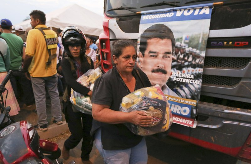 People carry bags with food provided by the Nicolas Maduro's government near the international bridge of Tienditas on the outskirts of Urena, Venezuela, Monday, Feb. (AP Photo/Fernando Llano)
