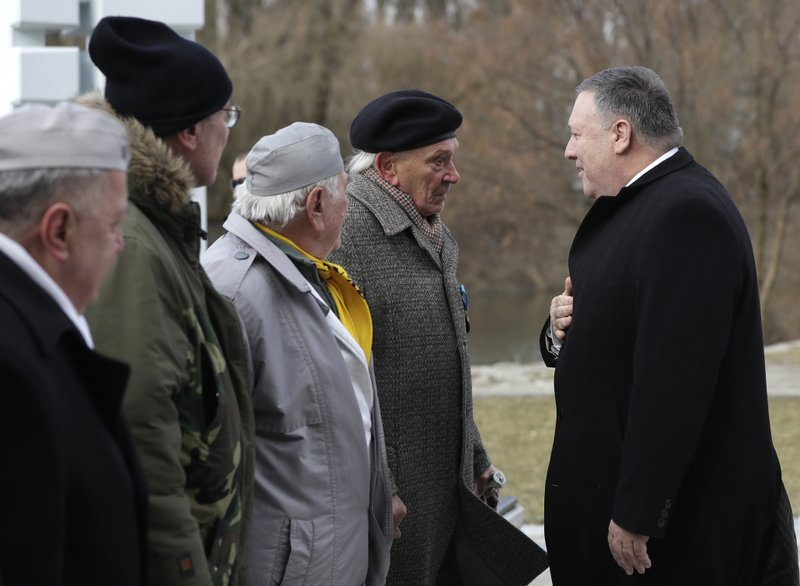 US Secretary of State Mike Pompeo , right, meets with members of Slovakia's confederation of political prisoners at the Freedom Gate memorial in Bratislava, Slovakia, Tuesday, Feb. (AP Photo/Petr David Josek)
