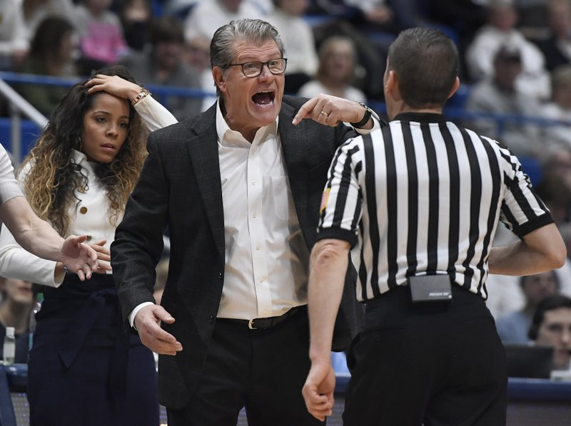Connecticut head coach Geno Auriemma reacts toward official Joseph Vaszily, right, as assistant coach Jasmine Lister, left, looks on, during the second half of an NCAA college basketball game against South Carolina, Monday, Feb. (AP Photo/Jessica Hill)