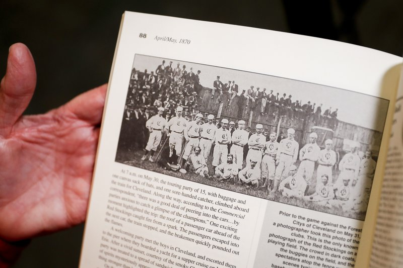 Greg Rhodes, the Cincinnati Reds baseball team historian, holds a copy of The First Boys of Summer to a page showing a photograph of the Cincinnati Red Stockings in 1870 during an interview at the Cincinnati Reds Hall of Fame, Tuesday, Jan. (AP Photo/John Minchillo)