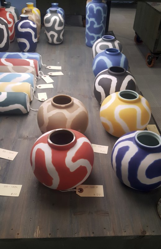 This Feb. 3, 2019 photo shows pieces at the NY NOW Show in New York. At Middle Kingdom, the Memphis movement was evoked in a collection of vibrantly hued vases with a bold swirl pattern. (Kim Cook via AP)