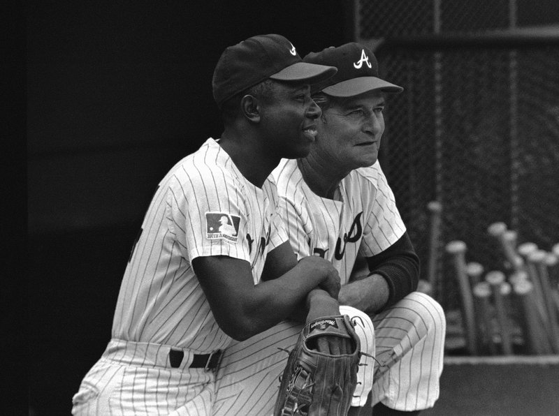 FILE - In this Sept. 30, 1969, file photo, a Major League Baseball 100th anniversary patch is shown on the uniform of Atlanta Braves team captain Hank Aaron, left, as he watches from the dugout with manager Luman Harris, during a game against the San Diego Padres, in Atlanta. (AP Photo/Joe Holloway Jr., File)