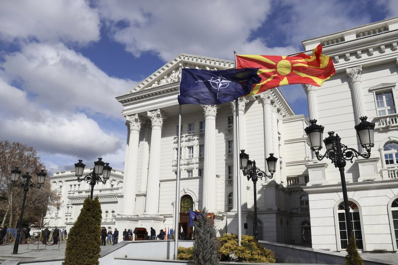 Macedonian, right, and NATO flag wave in front of the government building during a ceremony in Skopje, Tuesday, Feb. (AP Photo/Dragan Perkovksi)