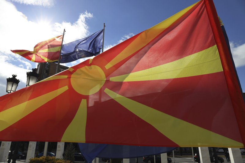 Macedonian and NATO flag wave in front of the government building during a ceremony in Skopje, Tuesday, Feb. (AP Photo/Dragan Perkovksi)