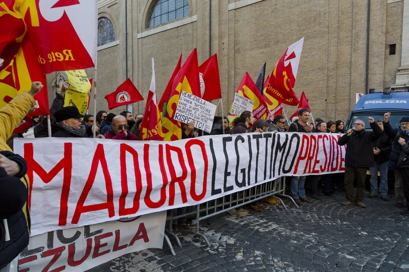 Demonstrators hold banners and placards during a pro-Maduro demonstration in downtown Rome, Tuesday, Feb. (AP Photo/Domenico Stinellis)