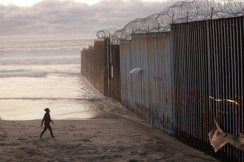 FILE - In this Jan. 9, 2019 file photo, a woman walks on the beach next to the border wall topped with razor wire in Tijuana, Mexico. (AP Photo/Gregory Bull, File)