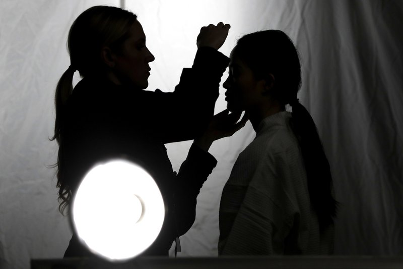 A makeup artist works on a model prior to a show displaying the Tom Ford collection during Fashion Week, Wednesday, Feb. (AP Photo/Julio Cortez)