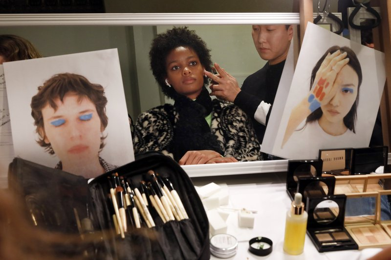 A model has make-up applied backstage before the the Carolina Herrera collection is modeled during Fashion Week in New York, Monday, Feb. (AP Photo/Richard Drew)