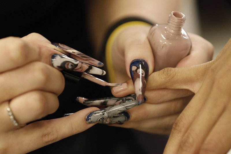 A manicurist wears cartoon-themed nails as she applies nail polish backstage to a model before the Carolina Herrera collection is modeled during Fashion Week in New York, Monday, Feb. (AP Photo/Richard Drew)