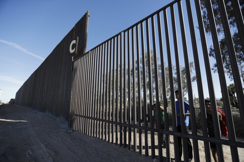 FILE - In this March 5, 2018, file photo, boys look through an older section of the border structure from Mexicali, Mexico, alongside a newly-constructed, taller section, left, in Calexico, Calif. (AP Photo/Gregory Bull, File)