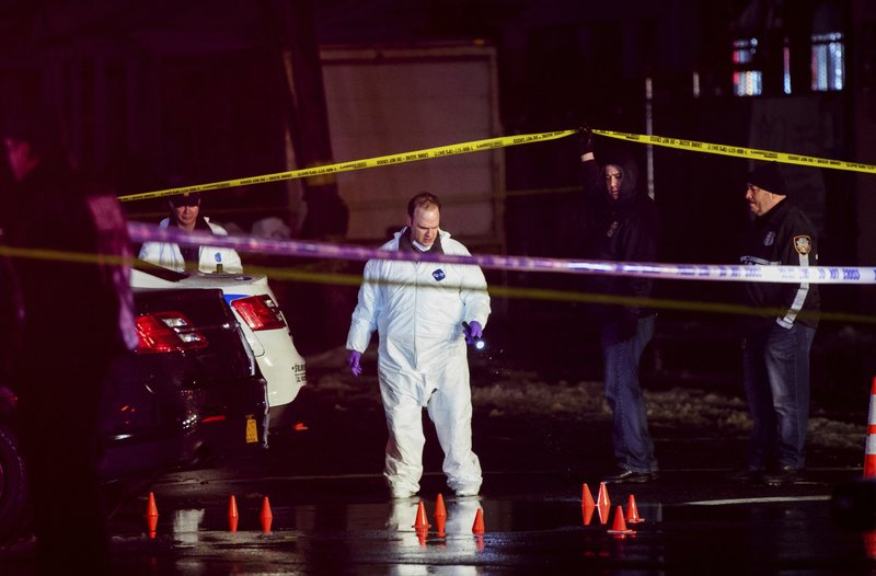 Investigators look over the area after a few New York City police officers were shot while responding to a robbery at a T-Mobile store in the Queens borough of New York on Tuesday, Feb. (AP Photo/Kevin Hagen)
