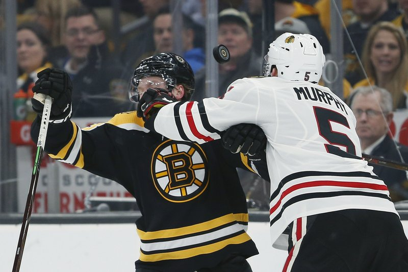 Chicago Blackhawks' Connor Murphy (5) and Boston Bruins' Danton Heinen compete for the puck during the second period of an NHL hockey game in Boston, Tuesday, Feb. (AP Photo/Michael Dwyer)