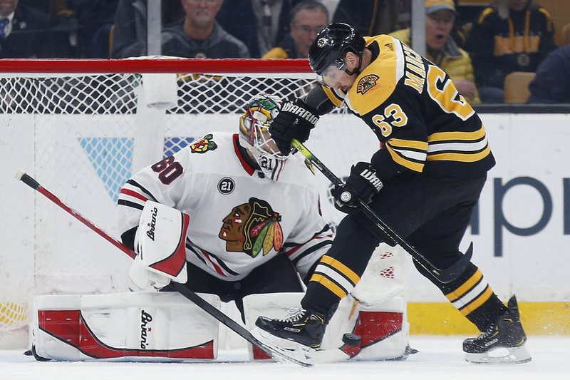 Boston Bruins' Brad Marchand (63) tries to get a shot on Chicago Blackhawks' Collin Delia (60) during the first period of an NHL hockey game in Boston, Tuesday, Feb. (AP Photo/Michael Dwyer)