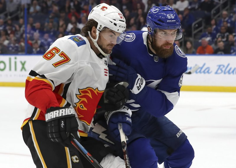 Calgary Flames' Michael Frolik, left, of the Czech Republic, goes into the boards for a loose puck against Tampa Bay Lightning's Braydon Coburn during the first period of an NHL hockey game Tuesday, Feb. (AP Photo/Mike Carlson)