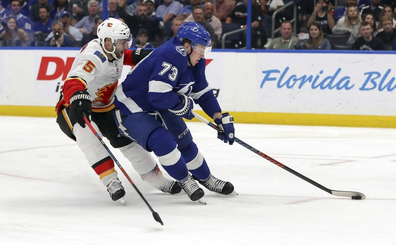 Tampa Bay Lightning's Adam Erne avoids the check of Calgary Flames' Mark Giordano during the second period of an NHL hockey game Tuesday, Feb. (AP Photo/Mike Carlson)