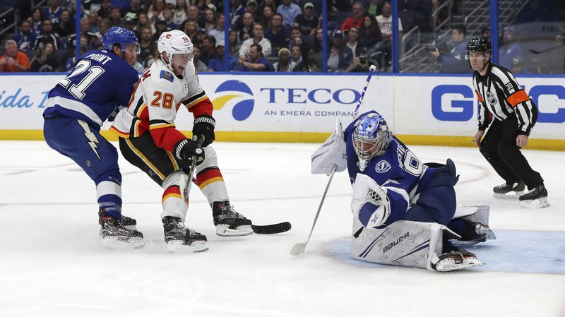 Tampa Bay Lightning goaltender Andrei Vasilevskiy, of Russia, makes a save against Calgary Flames' Elias Lindholm, of Sweden, as Brayden Point (21) defends during the first period of an NHL hockey game Tuesday, Feb. (AP Photo/Mike Carlson)
