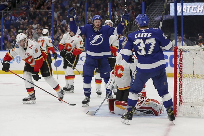 Tampa Bay Lightning's Yanni Gourde (37) and Anthony Cirelli celebrate a goal as Calgary Flames goaltender David Rittich, of the Czech Republic, and Mark Giordano (5) react during the second period of an NHL hockey game Tuesday, Feb. (AP Photo/Mike Carlson)
