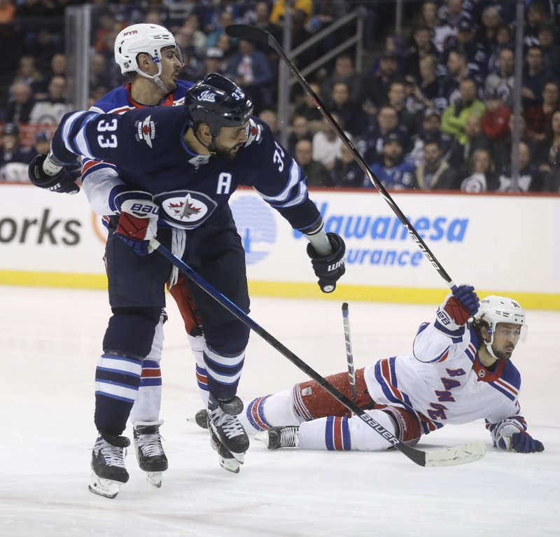 Winnipeg Jets defenceman Dustin Byfuglien (33) gets tied up with New York Rangers left wing Chris Kreider (20) and right wing Mats Zuccarello (36) during the second period of an NHL hockey game Tuesday, Feb. (Trevor Hagan/The Canadian Press via AP)