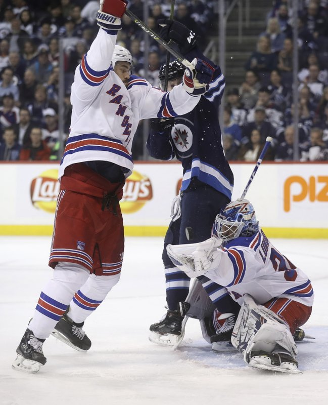 New York Rangers goaltender Henrik Lundqvist (30) makes a glove save as defenseman Adam McQuaid (54) battles with Winnipeg Jets left wing Kyle Connor (81) in front of the net during the second period of an NHL hockey game Tuesday, Feb. (Trevor Hagan/The Canadian Press via AP)