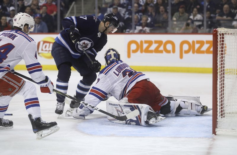 Winnipeg Jets center Adam Lowry (17) is stopped by New York Rangers goaltender Henrik Lundqvist (30) during the second period of an NHL hockey game Tuesday, Feb. (Trevor Hagan/The Canadian Press via AP)