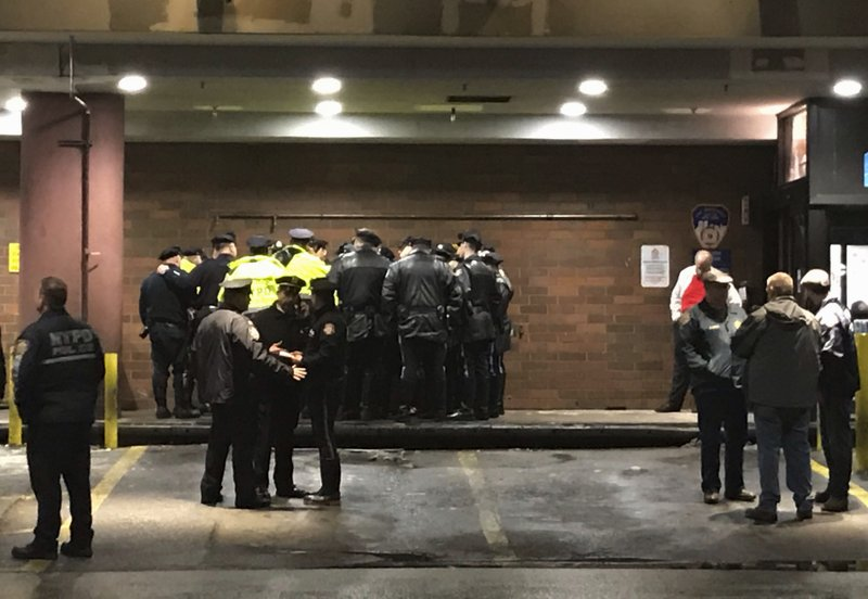 New York City police officers gather at Jamaica Hospital in the Queens borough of New York after a few NYPD officers while responding to a robbery in a mobile phone store on Tuesday, Feb. (AP Photo/Stephen Groves)