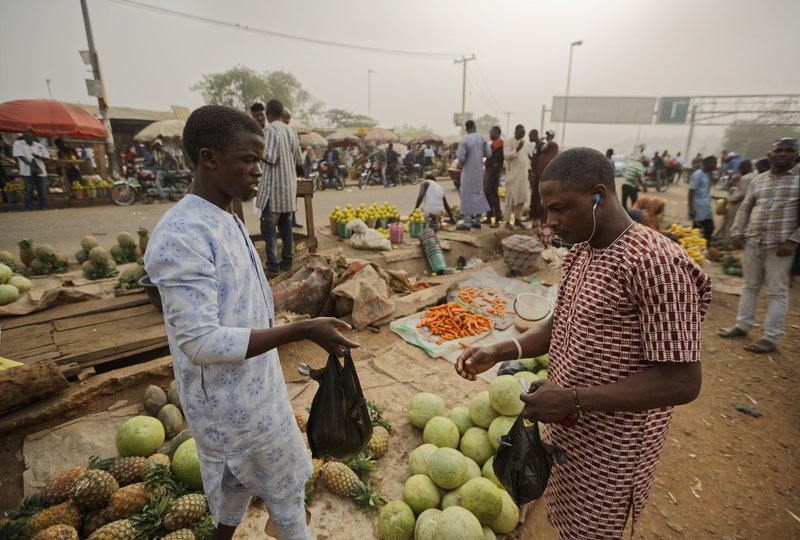 A customer, right, buys fruit from a street seller by the side of the road at a busy intersection near Nyanya, on the eastern outskirts of the capital Abuja, Nigeria Tuesday, Feb. (AP Photo/Ben Curtis)