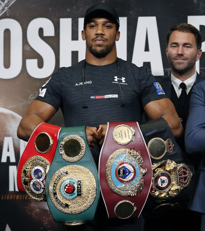 FILE - In this Sept. 20, 2018, file photo, boxer Anthony Joshua, of Britain, foreground, poses with boxing promoter Eddie Hearn after a press conference for Joshua's fight against Russia's Alexander Povetkin, at Wembley stadium in London. (AP Photo/Frank Augstein, File)