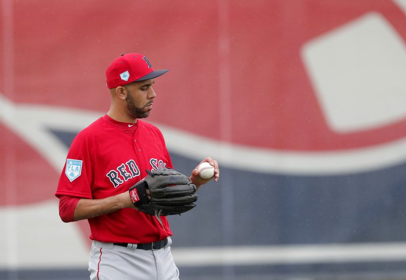 Boston Red Sox starting pitcher David Price looks at a ball as he warms up at the team's spring training baseball facility in Ft. (AP Photo/Gerald Herbert)