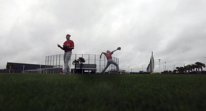 Boston Red Sox starting pitchers Nathan Eovaldi, left, and Chris Sale, warm up in the rain as pitchers and catchers report for their first workout at their spring training baseball facility in Ft. (AP Photo/Gerald Herbert)