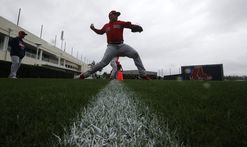 Boston Red Sox pitcher Erasmo Ramírez warms up as pitchers and catchers report for their first workout at the Boston Red Sox spring training baseball facility in Ft. (AP Photo/Gerald Herbert)