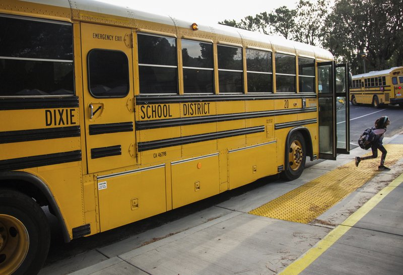 FILE - In this Oct. 18, 2018 file photo, a student hops off the school bus at Dixie Elementary School in San Rafael, Calif. (Gabrielle Lurie/San Francisco Chronicle via AP, File)