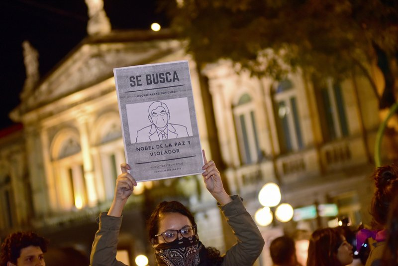 "A woman holds up a sign with a line drawing depicting Costa Rica's ex-President Oscar Arias and a message that reads in Spanish: ""WANTED: Oscar Arias Nobel Peace Prize laureate and Violator"", during a protest by women activists under the slogan"