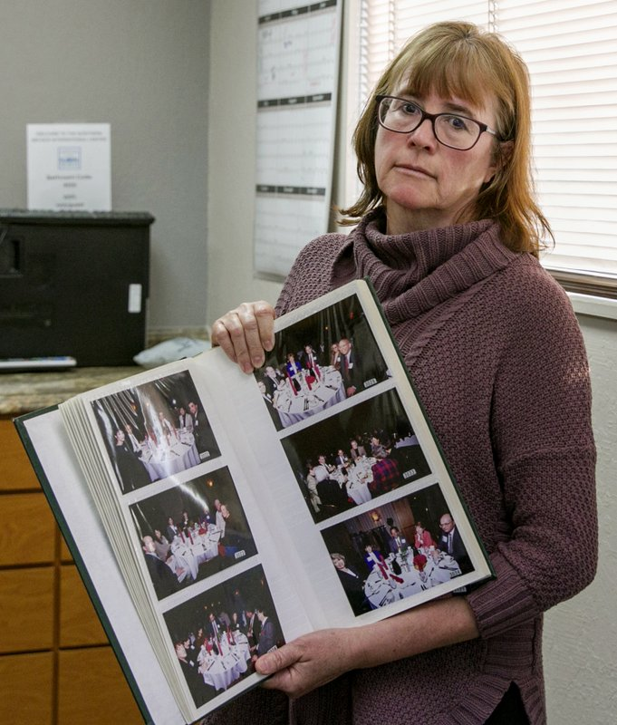 In this Monday, Feb. 11, 2019 photo, Carina Black poses in her office in Reno, Nev., holding a photo album containing dozens of photos of a dinner she attended where Nobel Peace Prize winner and former Costa Rican President Oscar Arias spoke on April 6, 1998. (AP Photo/Tom R. Smedes)
