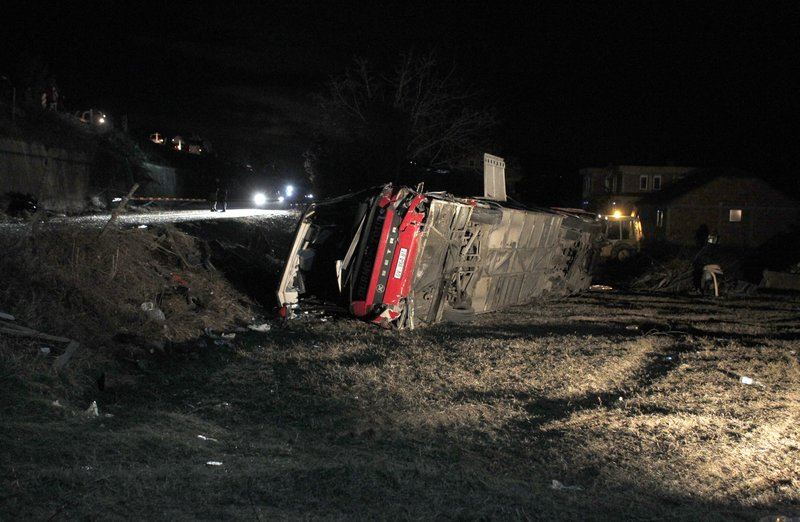 A bus lays overturned at the crash site at village of Laskarci, west of Skopje, North Macedonia, Wednesday, Feb. (AP Photo/Boris Grdanoski)