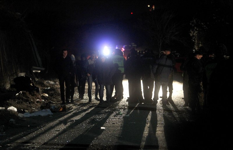 Police officers and investigators are silhouetted at the crash site at village of Laskarci, west of Skopje, North Macedonia, Wednesday, Feb. (AP Photo/Boris Grdanoski)