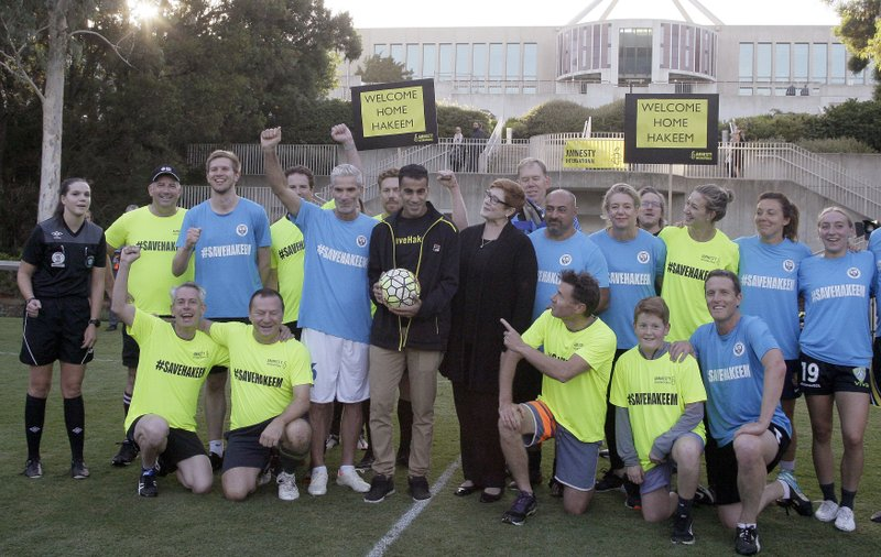 Refugee Hakeem al-Araibi, center with ball, former Australian national team captain Craig Foster, center left, and Australian Foreign Minister Marise Payne, center right, pose with soccer teams after a celebration match at Parliament House in Canberra, Australia, Thursday, Feb. (AP Photo/Rod McGuirk)
