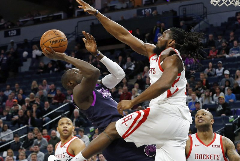Minnesota Timberwolves' Luol Deng, left, falls back as he shoots while Houston Rockets' Nene tries to block the shot in the first half of an NBA basketball game, Wednesday, Feb. (AP Photo/Jim Mone)