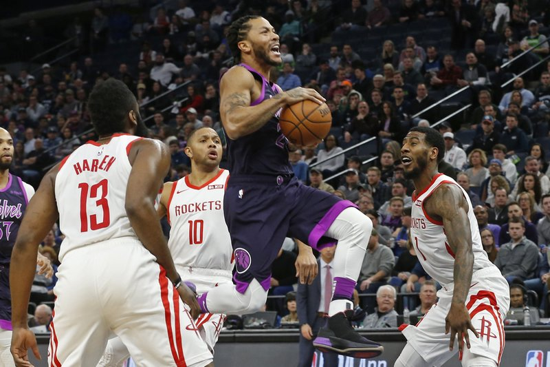 Minnesota Timberwolves' Derrick Rose, center, goes airborne for a layup as Houston Rockets' James Harden, left, Eric Gordon and Michael Carter-Williams, right, watch in the first half of an NBA basketball game, Wednesday, Feb. (AP Photo/Jim Mone)