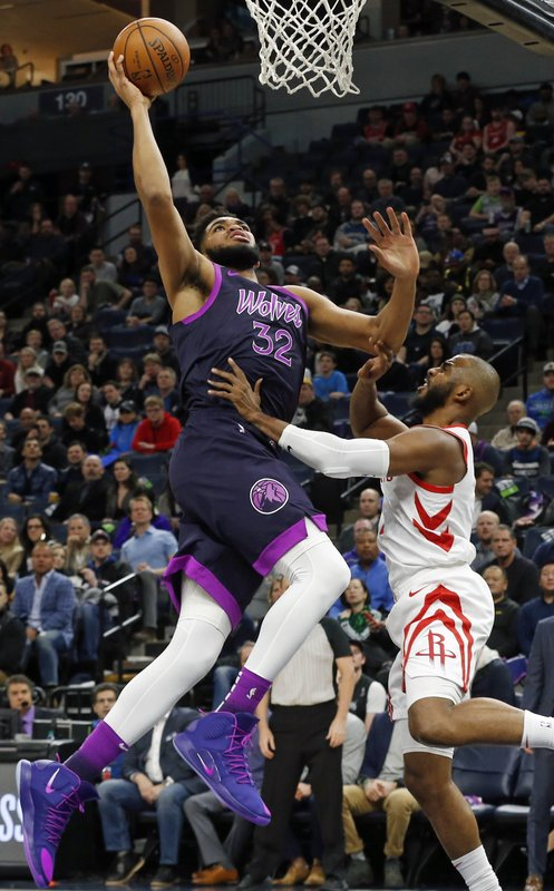 Minnesota Timberwolves' Karl-Anthony Towns, left, goes in for a layup as Houston Rockets' Chris Paul defends in the first half of an NBA basketball game, Wednesday, Feb. (AP Photo/Jim Mone)