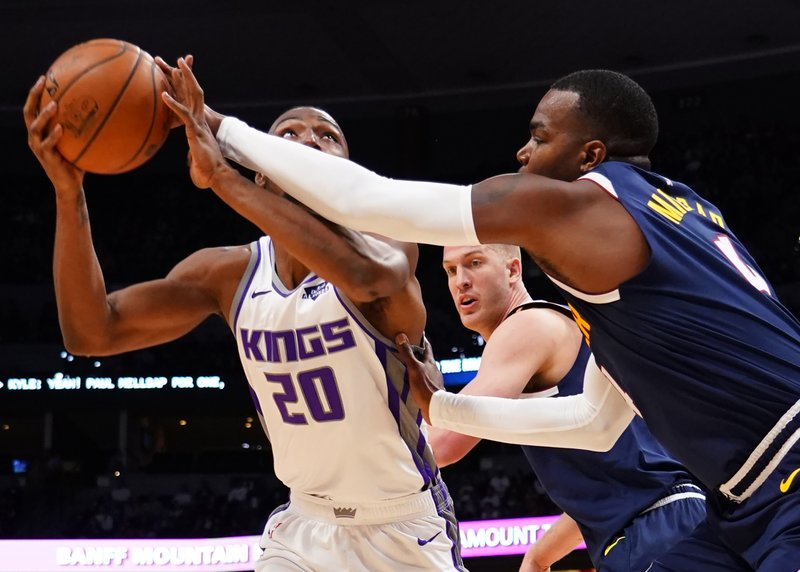 Denver Nuggets forward Paul Millsap (4) knocks the ball loose from the hands of Sacramento Kings forward Harry Giles III (20) as Denver Nuggets forward Mason Plumlee (24) looks on during the first half of an NBA basketball game Thursday, Feb. (AP Photo/Jack Dempsey)