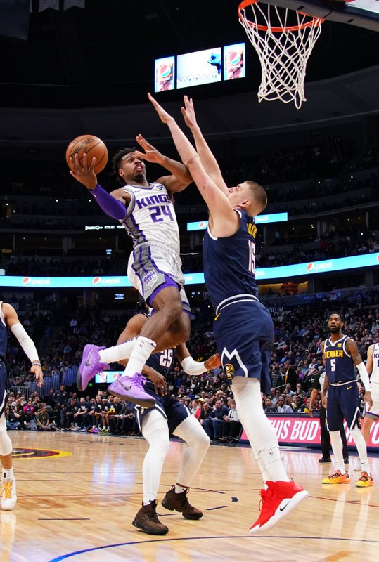 Sacramento Kings guard Buddy Hield (24) goes up for a shot against Denver Nuggets center Nikola Jokic (15) during the first half of an NBA basketball game Thursday, Feb. (AP Photo/Jack Dempsey)