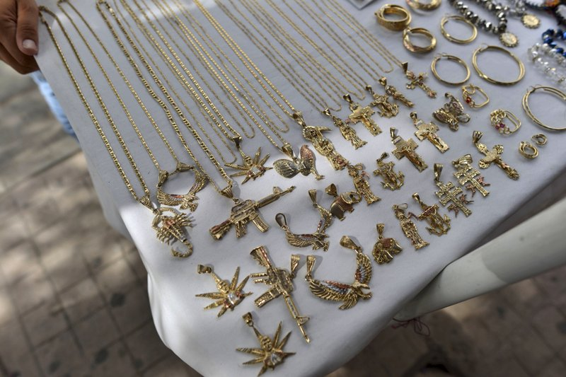 FILE - In this July 22, 2015 file photo, a man sells jewelry, many of it with narco-culture imagery, in downtown Culiacan, Mexico. (AP Photo/Fernando Brito, File)