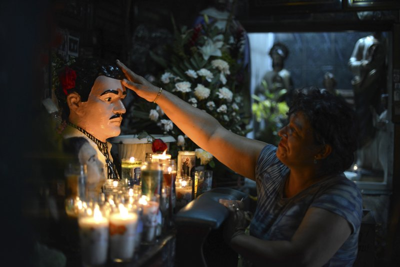 FILE - In this July 20, 2015 file photo, Guadalupe Tadeo de Valenzuela prays to folk-saint Jesus Malverde, to heal her sick daughter in the saint's chapel in Culiacan, Mexico. (AP Photo/Fernando Brito, File)